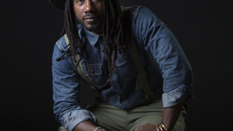 A Black man is sitting against a black backdrop. He is wearing a hat, denim shirt, green overalls, and jewelry.