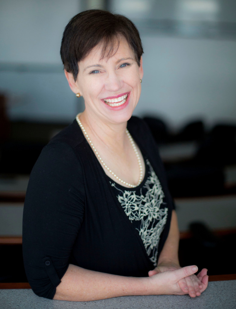 A white woman with short brown hair is smiling at the camera. She is wearing a black top and sweater, with a pearl necklace and earrings.