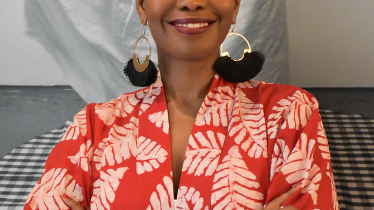 A Black woman wearing a red and white patterned top, a headwrap, and big earrings smilingat the camera. Her arms are crossed and she is standing in front of a black and white image.