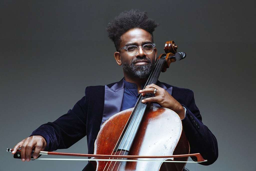 A Black man wearing a purple suit and glasses playing a cello, against a grey wall.