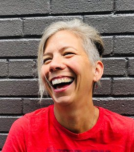 A White woman with grey hair is laughing, looking to the side. She is wearing a bright red top and is standing against a grey brick wall.