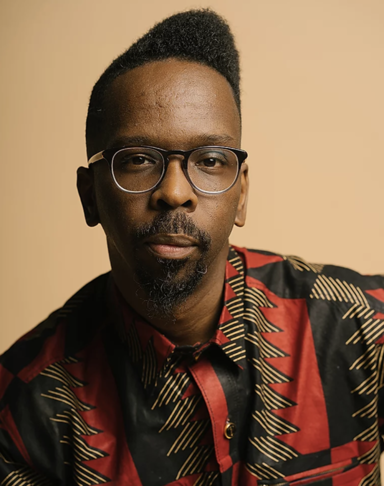 A Black man with facial hair in a red, black, and tan patterned collard shirt looking straight ahead. He is wearing glasses and against a brown wall.