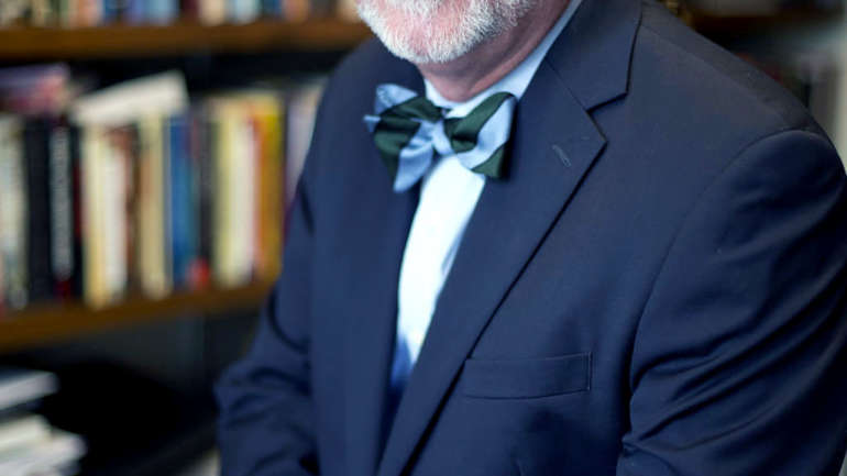A white man with facial hair and hair pulled back staring ahead. He is in a blue suit with a blue and green bowtie. He is standing in front of a case of books.