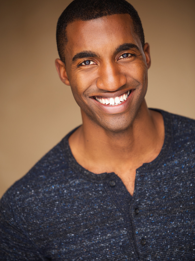 A Black man is smiling straight at the camera. He is wearing a dark blue button up shirt and is against a brown wall.