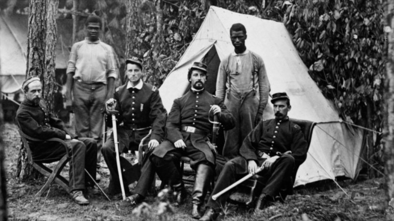 A black and white photo from the Civil War of four white male soldiers sitting down. Behind them are two Black men standing. They are outside with a tent in the background.
